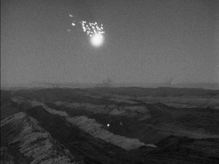 Eine Leuchtrakete erhellt den Tagebau.