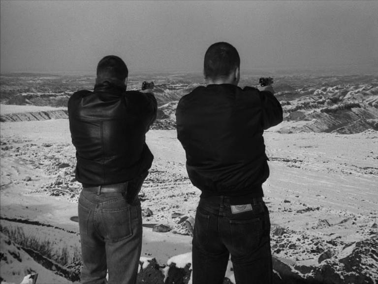 Zwei junge Männer schießen in den Tagebau.